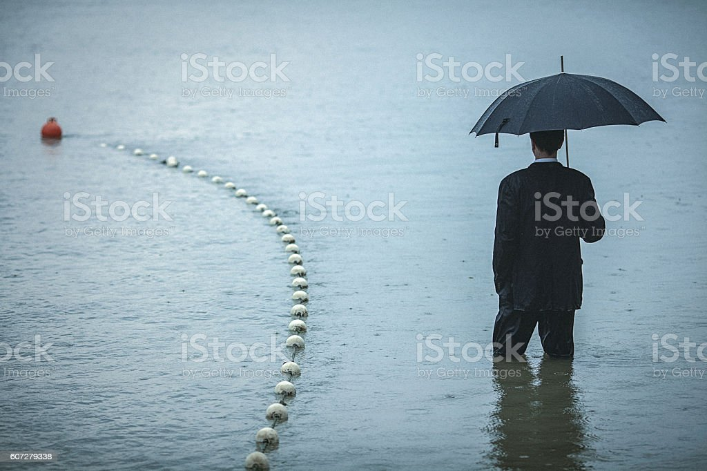 Handsome man wearing suit and holding umbrella, stands in water stock photo