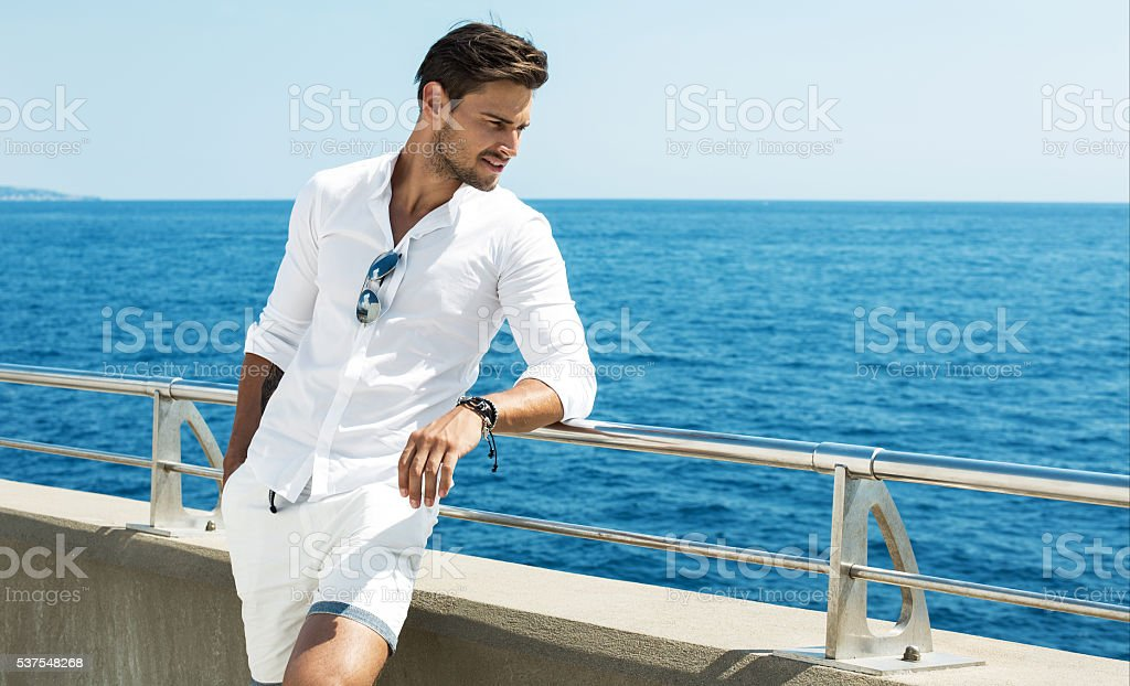 Handsome man wearing white clothes posing in sea scenery stock photo