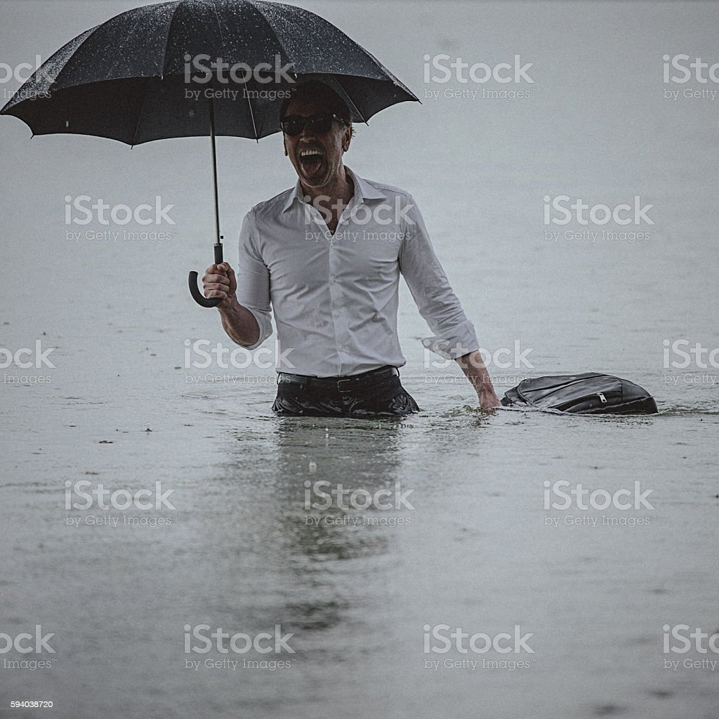 Handsome man wearing white shirt and holding umbrella during rain stock photo