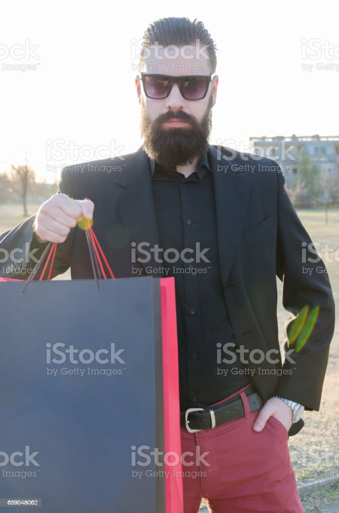 handsome man with a beard in a suit shows shopping bags with space for text, high key stock photo