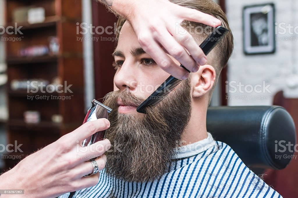 Handsome man with a long mustache in barbershop stock photo