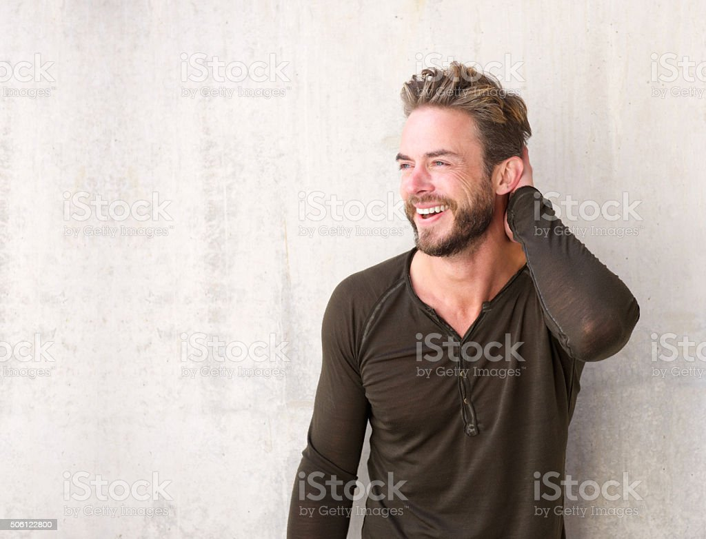 Handsome man with beard laughing with hand in hair stock photo