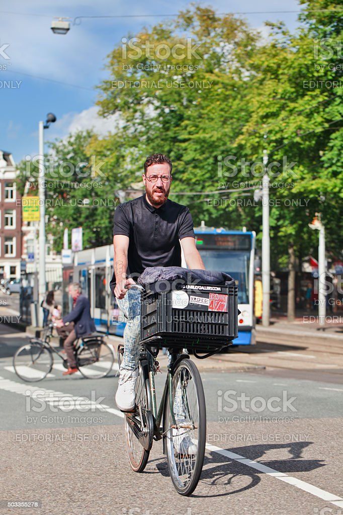 Handsome man with beard on a bicycle with a crate stock photo