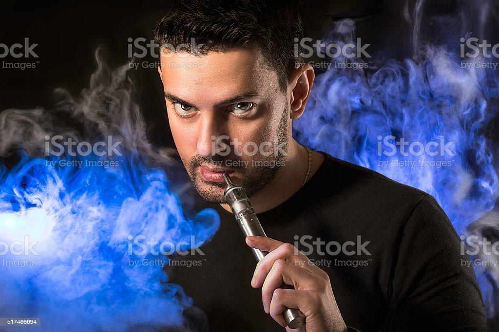 Handsome man with e-cirarette in a vapor stock photo