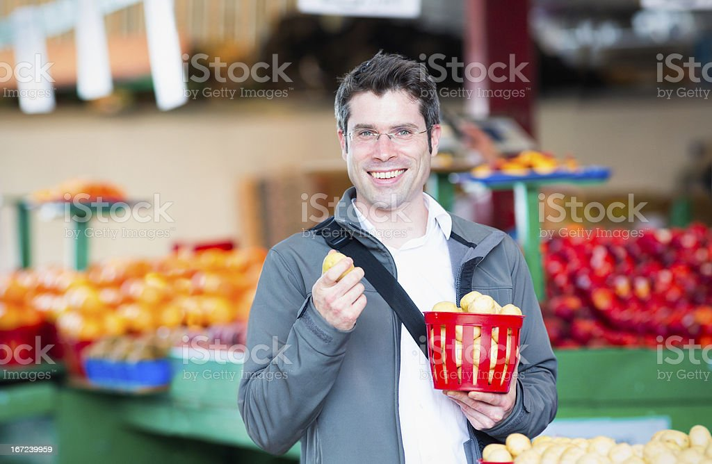 Handsome man with fresh organic potatoes at the market stock photo