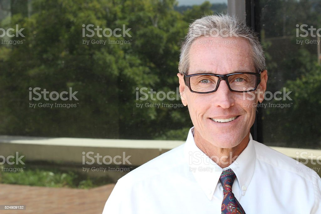 Handsome man with grey hair and specs stock photo