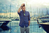 Handsome man with luxury yachts in port.