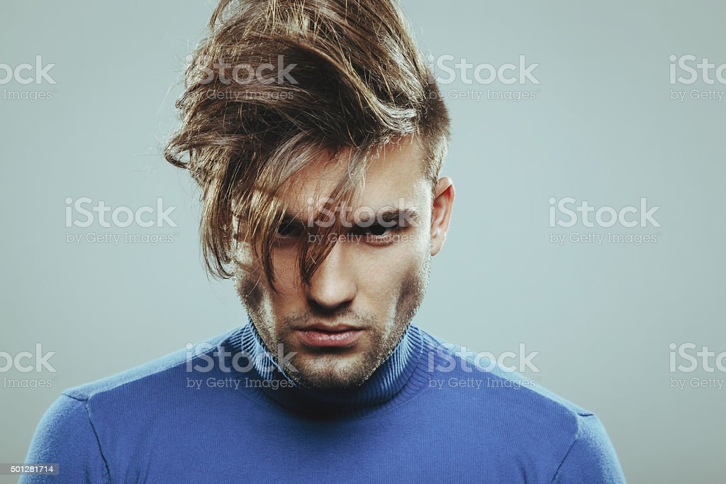 Handsome man with modern hairstyle in studio stock photo