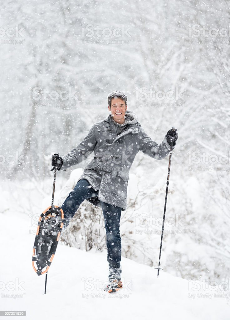 Handsome Man with Snowshoes out in a Snow Storm stock photo