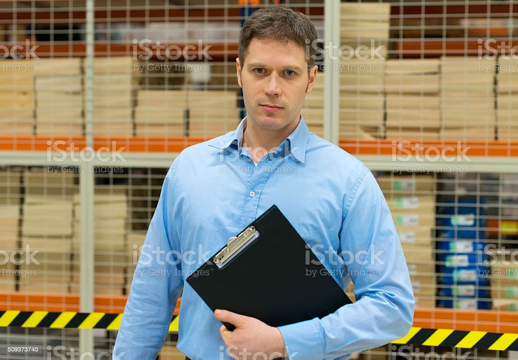 Handsome manager with clipboard in post office. stock photo