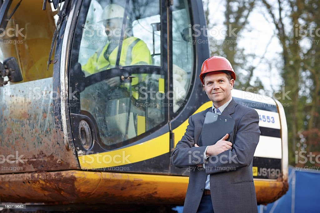Handsome mature architect with a excavator royalty-free stock photo