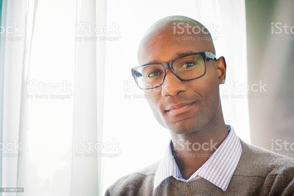 Handsome mature black male bald intellectual portrait by window stock photo