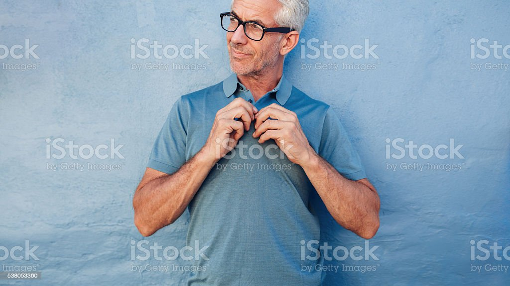 Handsome mature man buttoning up his tshirt stock photo