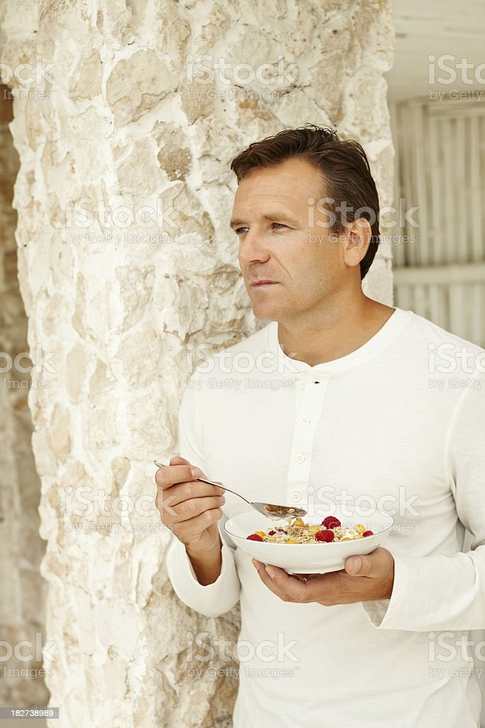 Handsome mature man eating breakfast outdoors stock photo