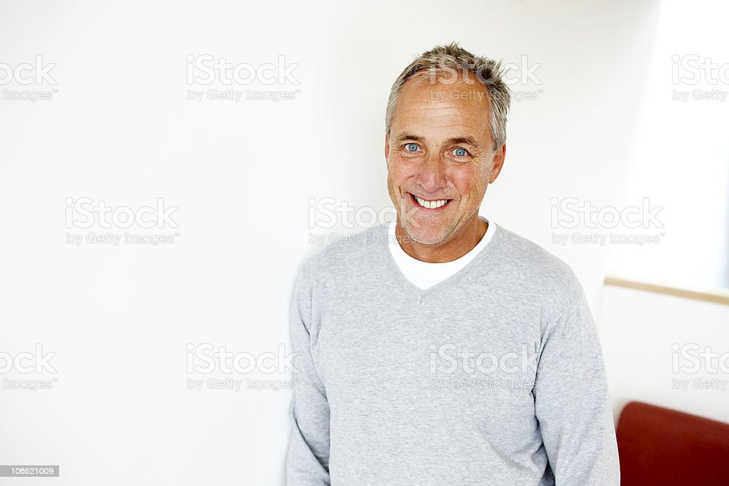 handsome mature man leaning against a wall smiling royalty-free stock photo