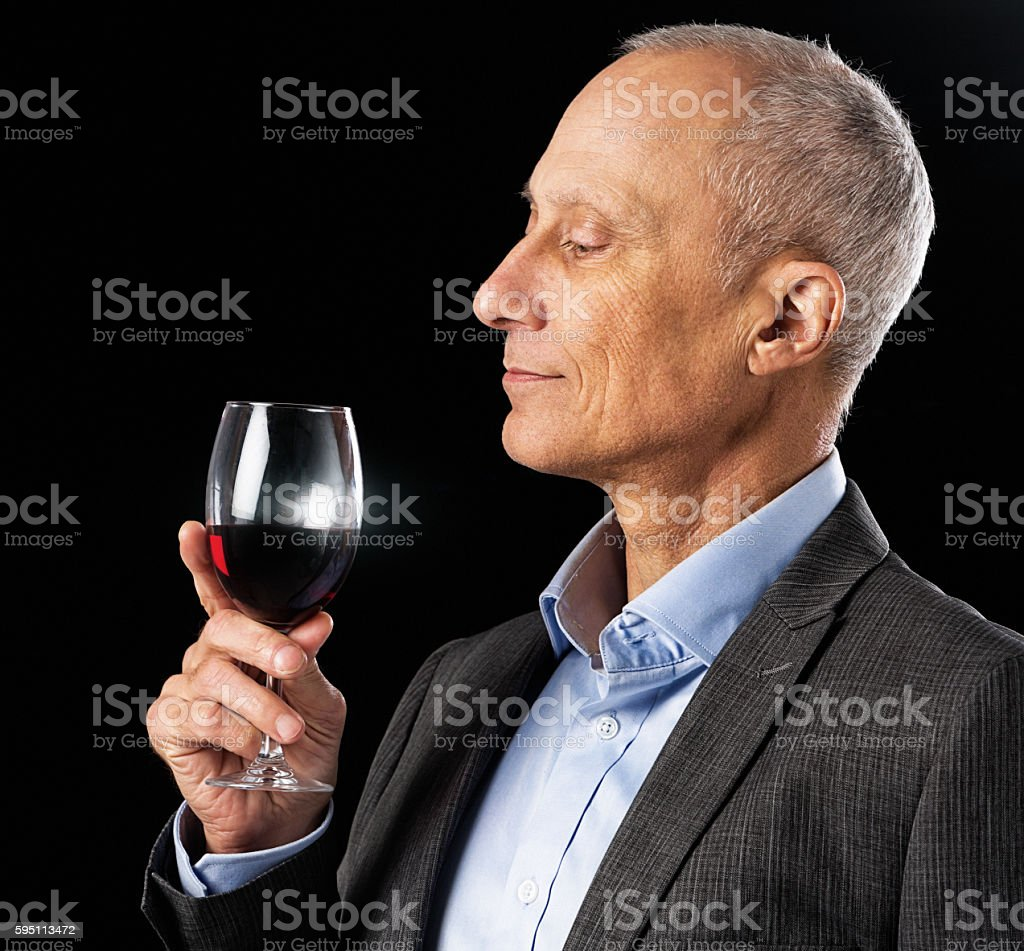 Handsome mature man looks appreciatively at glass of red wine stock photo