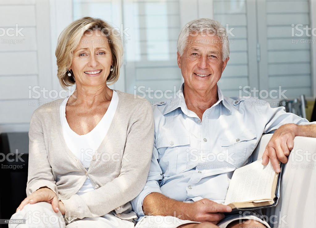 Handsome mature man reading book with wife on sofa royalty-free stock photo