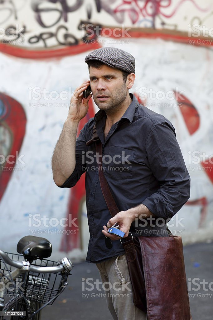 handsome mature man with flat cap at the phone stock photo