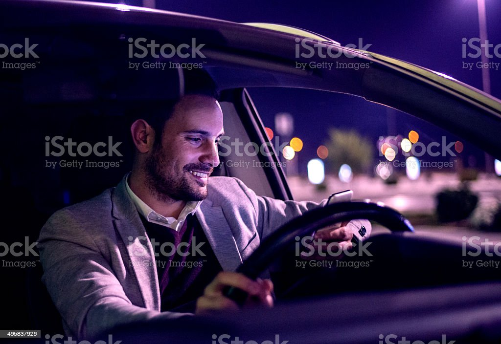 Handsome men sitting in a car. Man using smart phone. stock photo