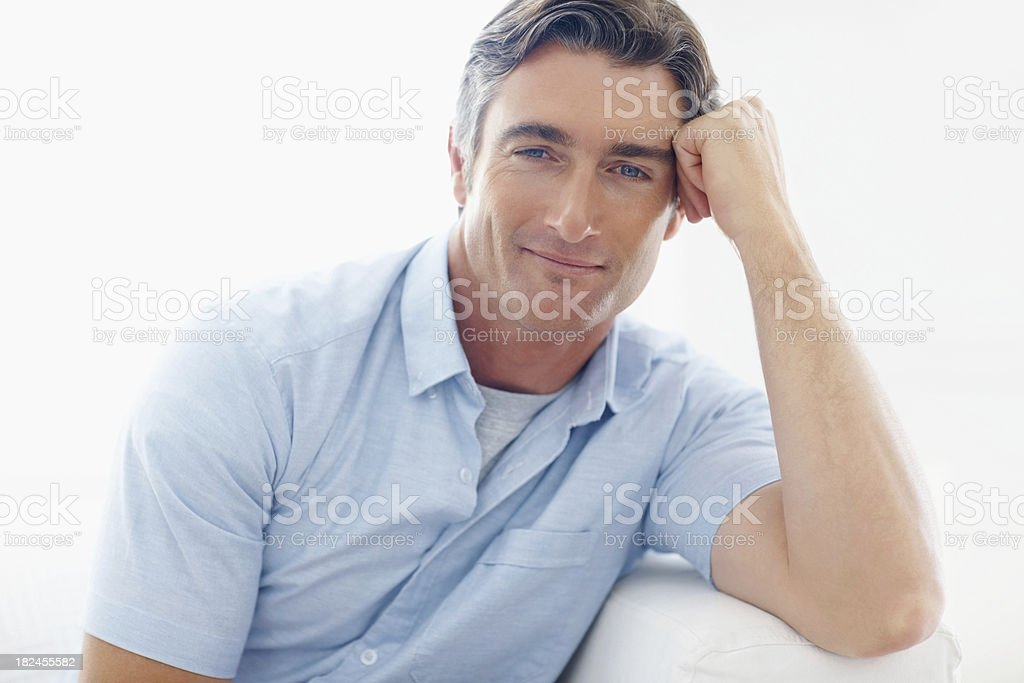 Handsome mid adult man sitting on couch royalty-free stock photo