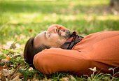 Handsome middle-aged man lying on the autumn leaves in