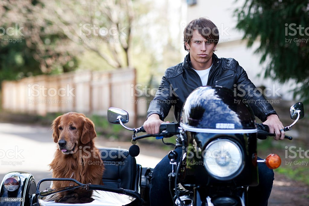 Handsome Motorcyclist with His Dog in the Side Car stock photo