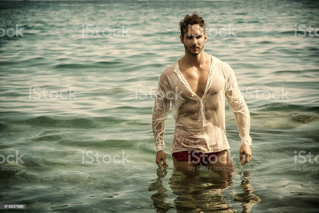 Handsome muscle man in the sea with wet shirt on stock photo