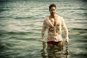 Handsome muscle man in the sea with wet shirt on