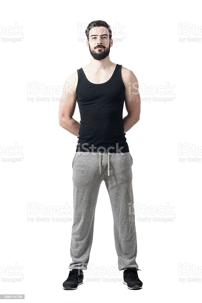 Handsome muscular athlete with hands behind back looking at camera stock photo