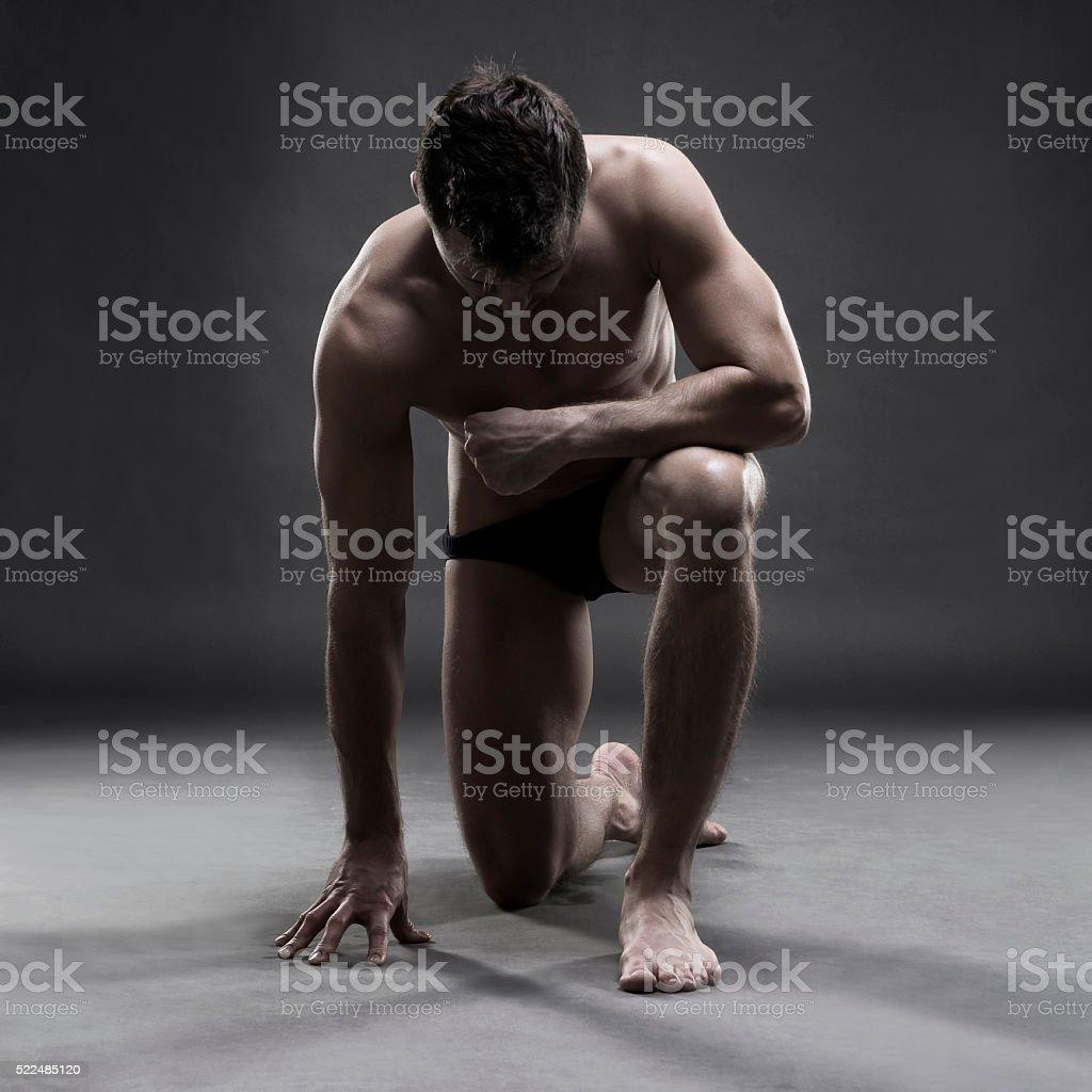 Handsome muscular bodybuilder posing on gray background stock photo