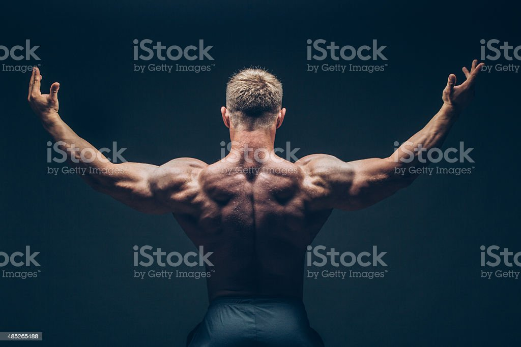 Handsome muscular bodybuilder posing over black background stock photo