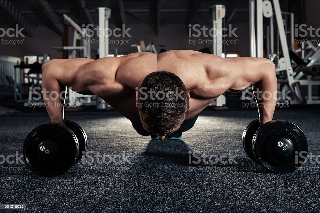 Handsome muscular man doing pushup exercise with dumbbell stock photo