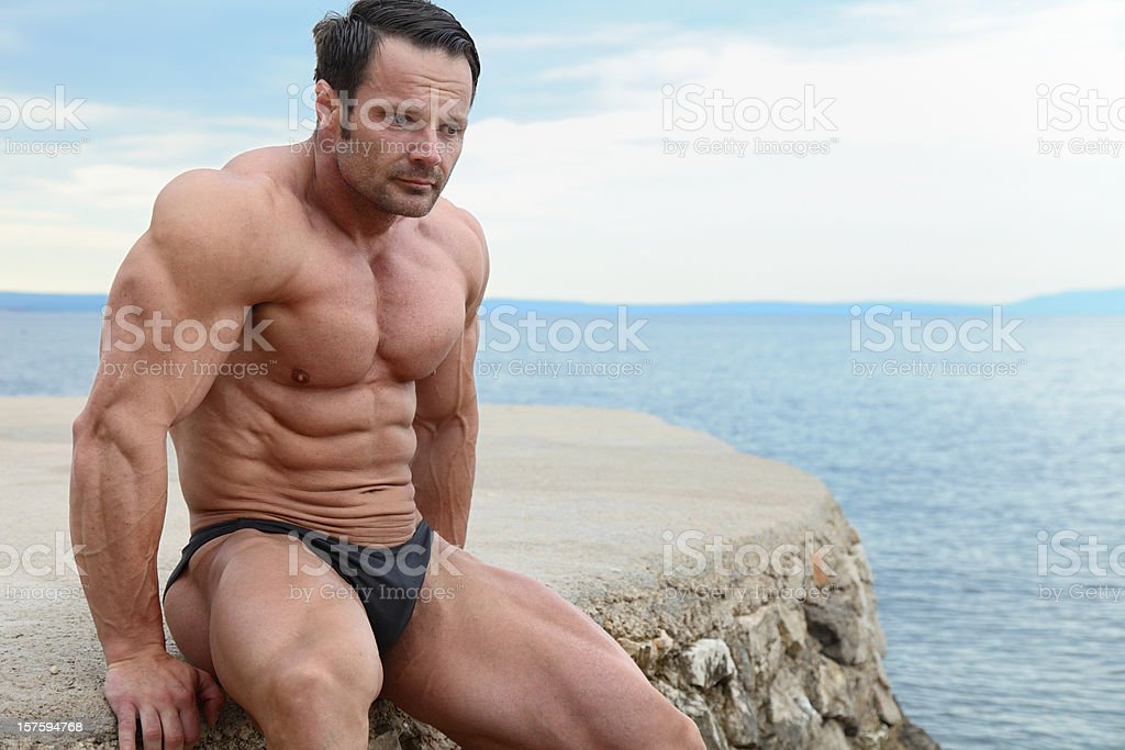 Handsome muscular man sitting on the beach royalty-free stock photo