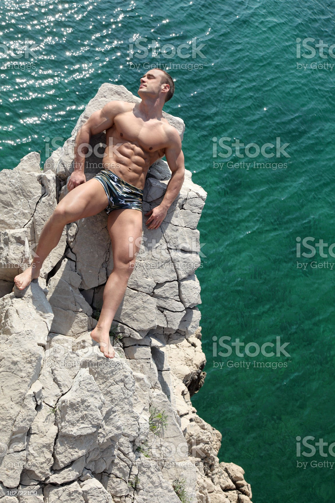 Handsome muscular man sunbathing on the beach royalty-free stock photo
