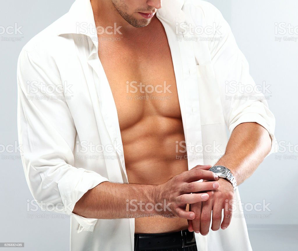 Handsome muscular man with a wristwatch. stock photo