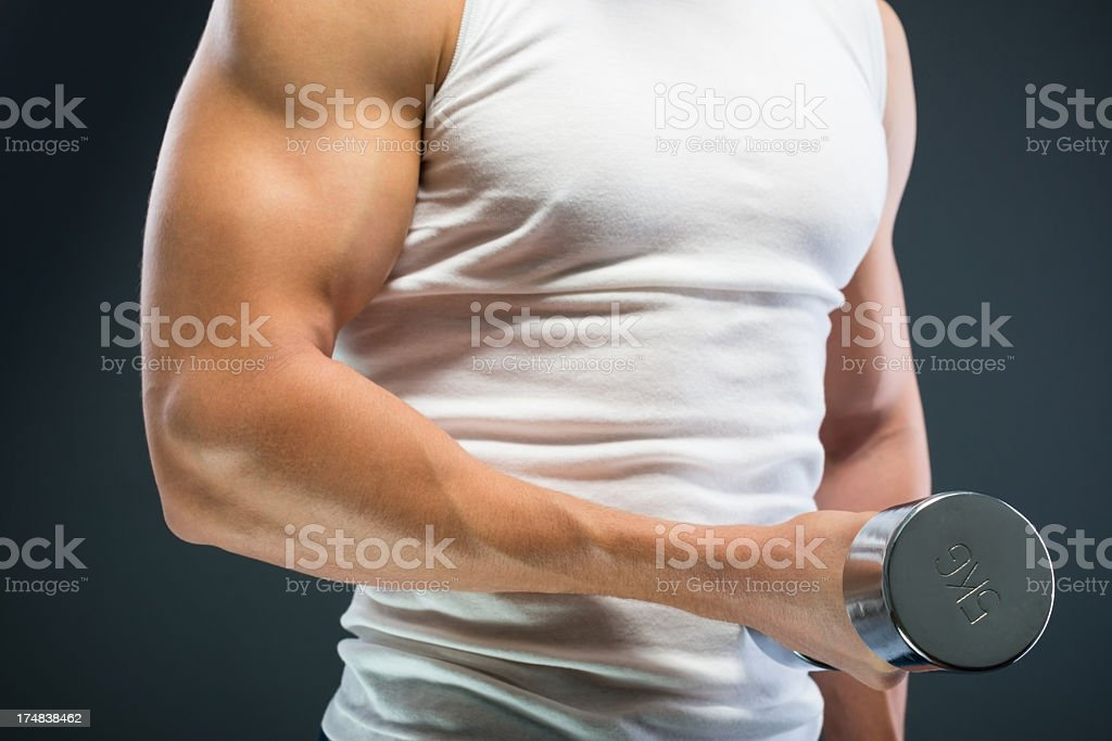 Handsome muscular man working out with  weights royalty-free stock photo