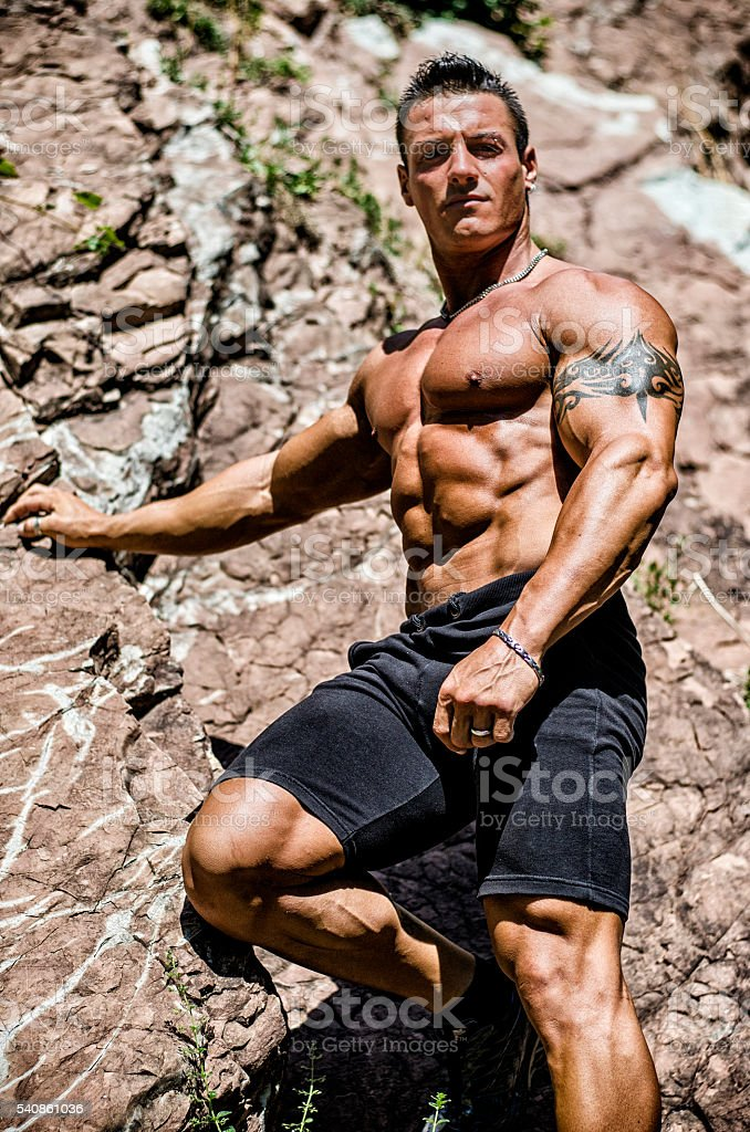 Handsome, muscular, shirless climber climbing rock stock photo