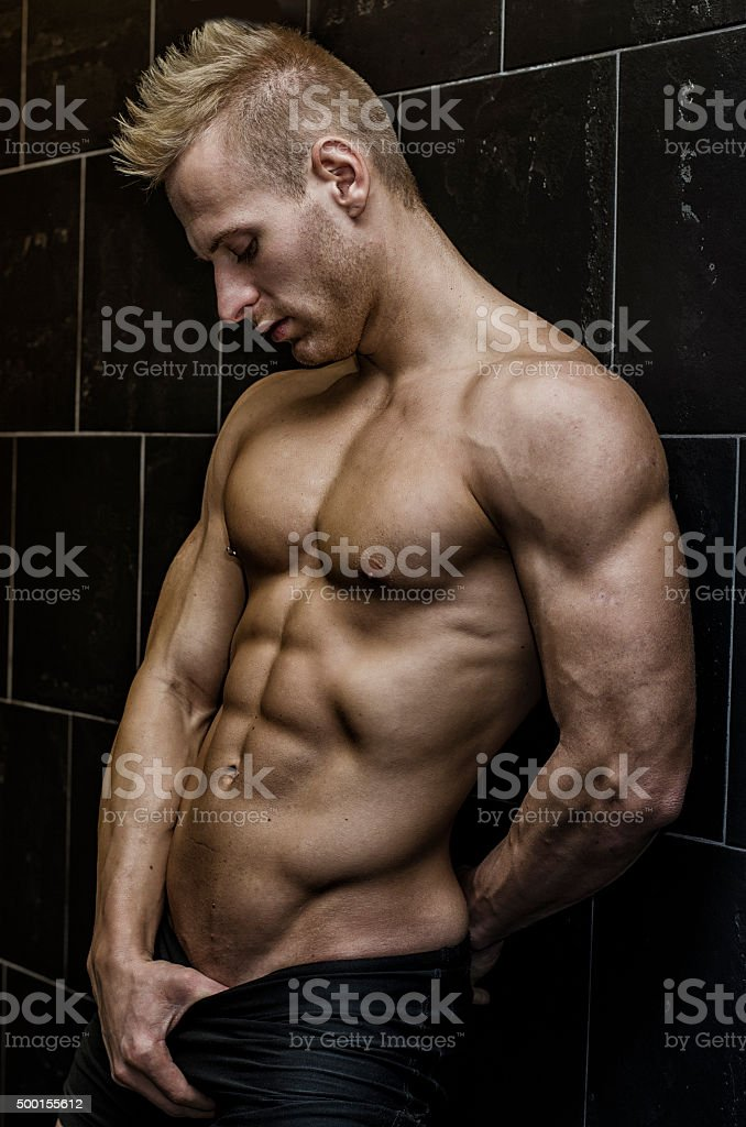 Handsome, muscular young man shirtless leaning against tiled wall stock photo