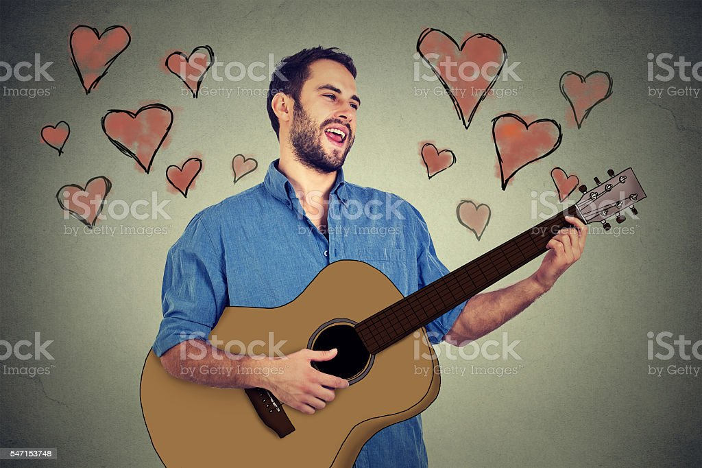 handsome musician man in love playing guitar singing stock photo