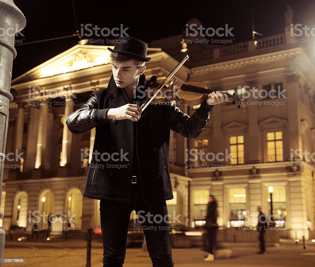 Handsome musician playing in a middle of the town stock photo