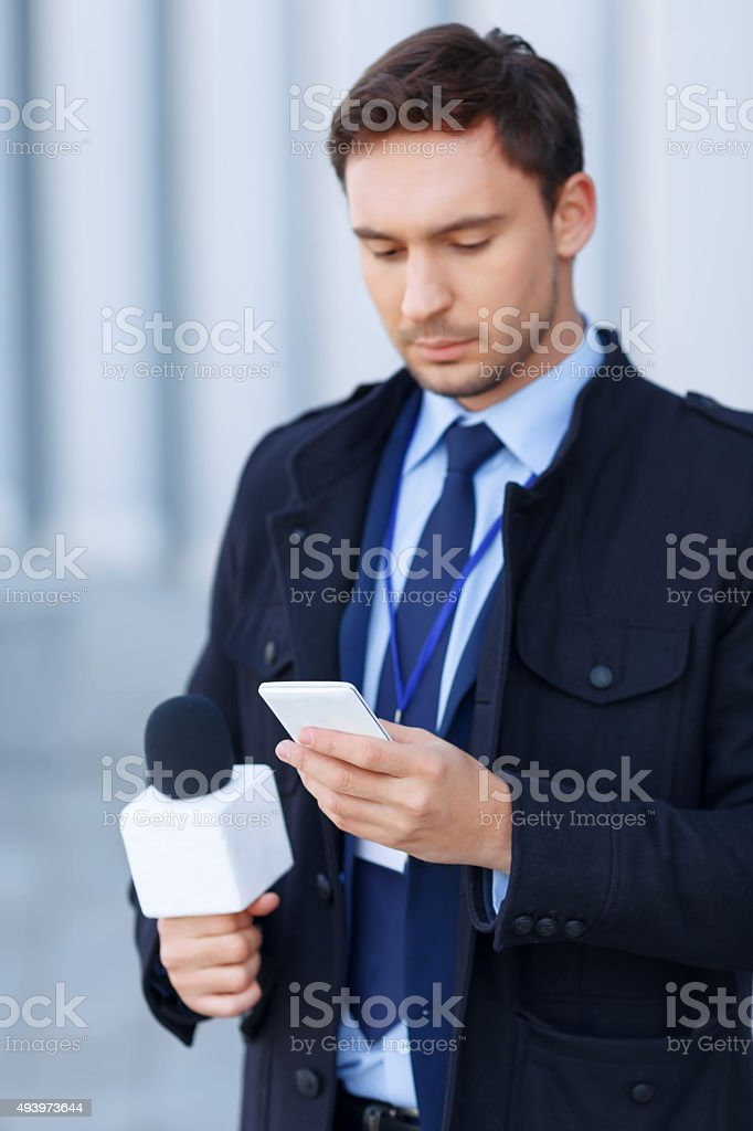 Handsome newsgatherer is busy working on the phone stock photo