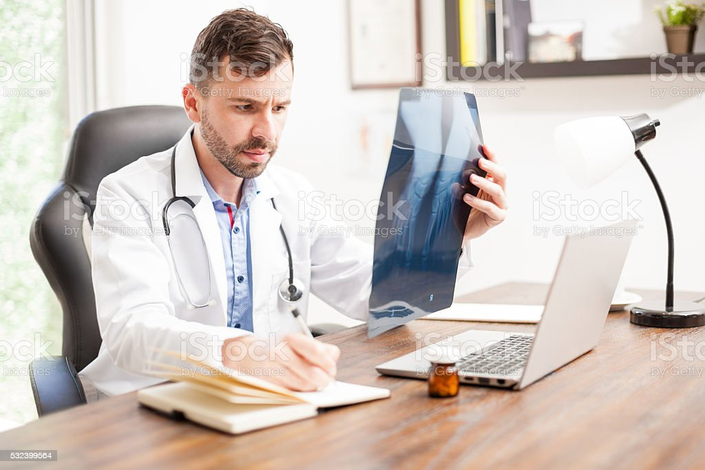Handsome orthopedist busy at work stock photo
