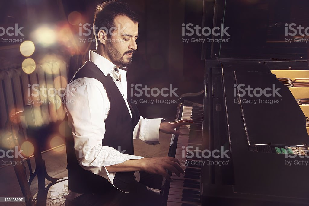 handsome piano player stock photo