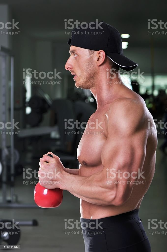 Handsome powerful athletic man doing biceps exercise with kettle bell stock photo