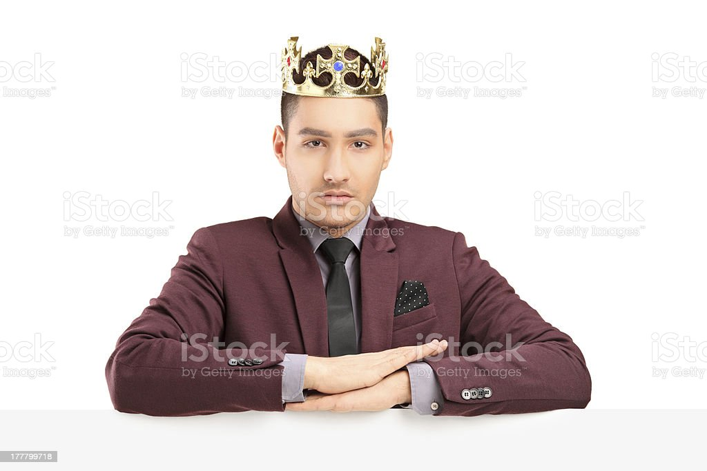 Handsome prince posing on a panel with diamond crown royalty-free stock photo