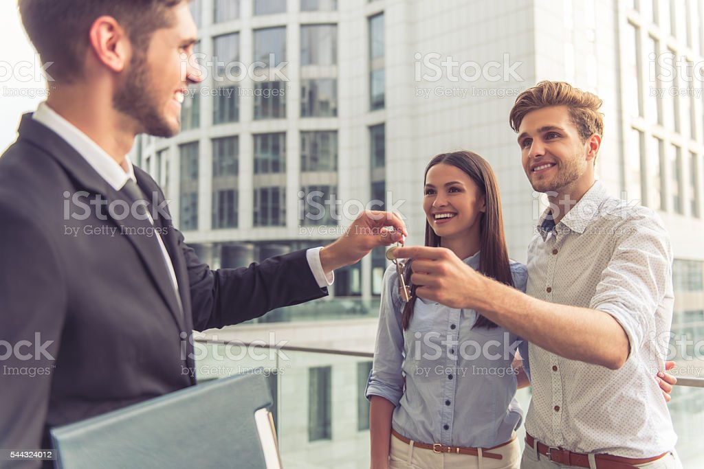 Handsome realtor and happy couple stock photo