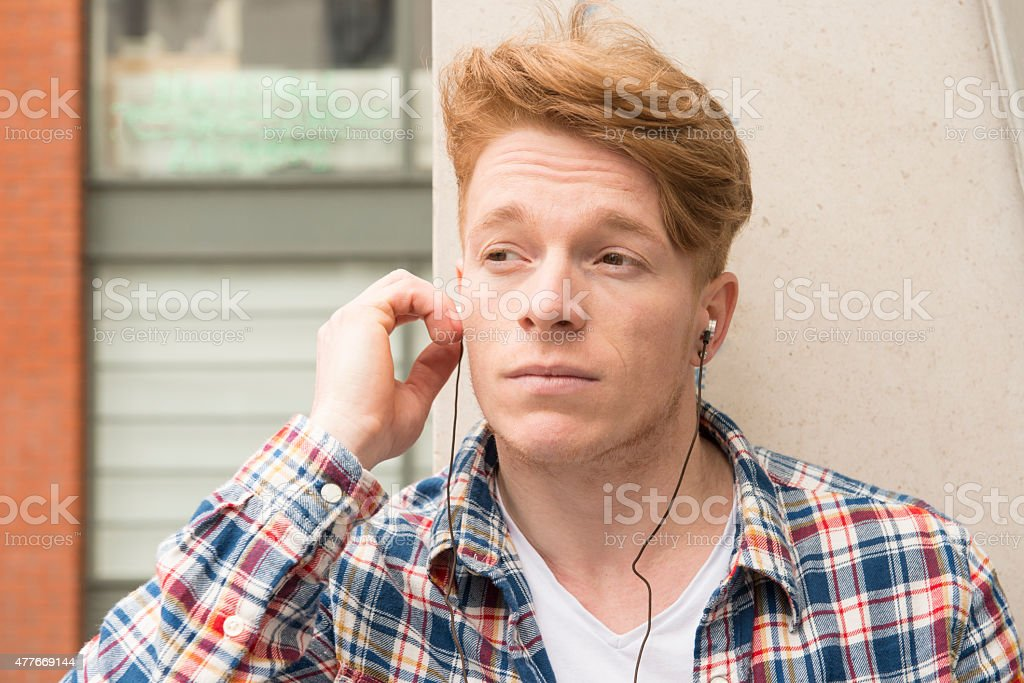 Handsome red haired man listening to music stock photo