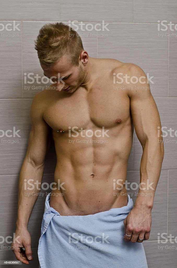 Handsome semi-naked young man in bathroom with towel royalty-free stock photo