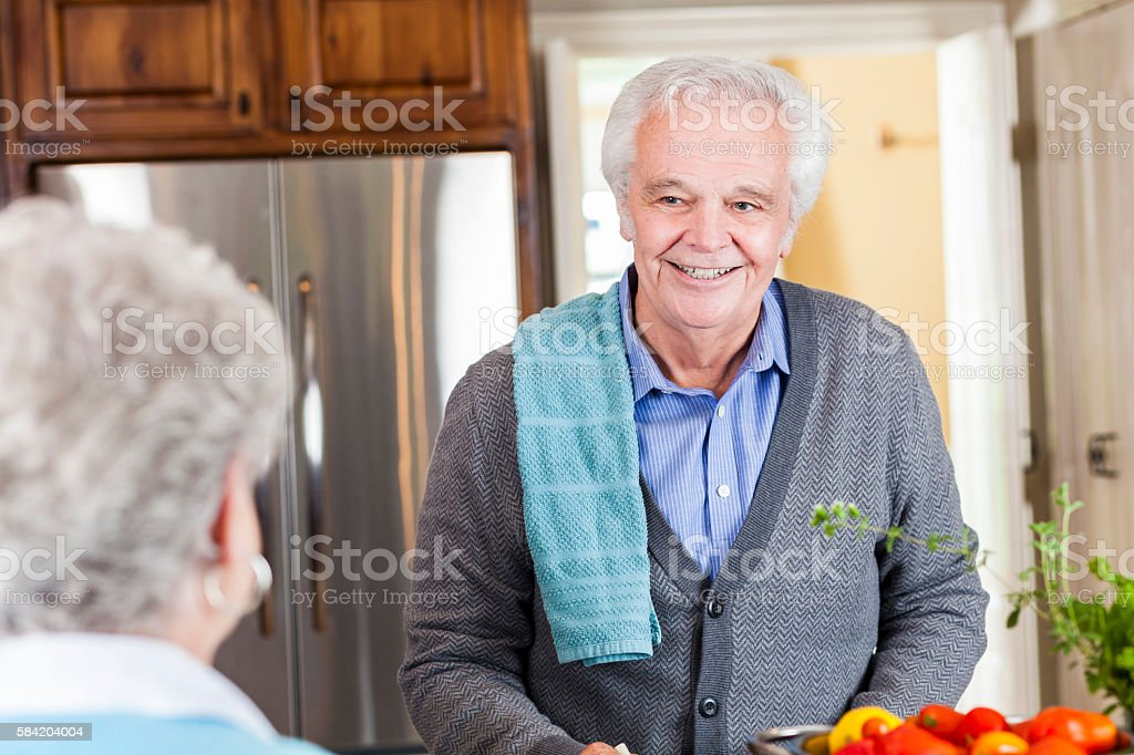 Handsome senior man cooking in a kitchen for her wife stock photo