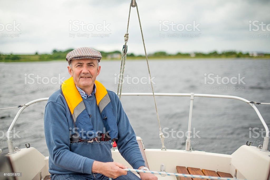 Handsome senior man sailing in the open waters stock photo